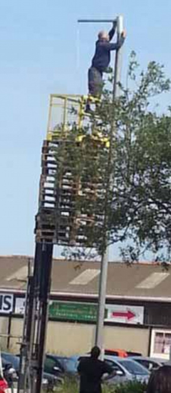 Picture of Balancing in a safety cage on a big stack of pallets? This guy is a safety nightmare