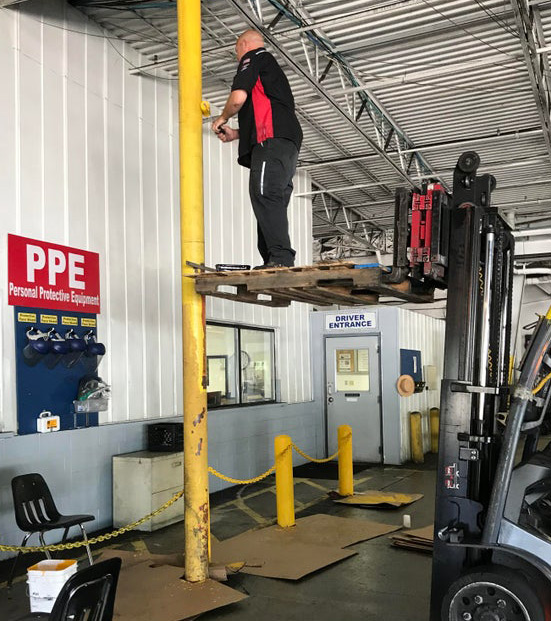 Picture of Painting from an unsafe pallet? Use a scissor lift instead!
