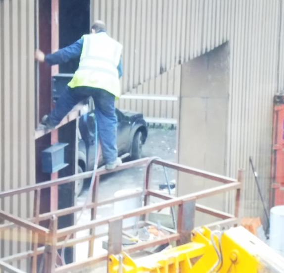 Picture of Balancing on a scissor lift edge with a torch in hand, utter madness