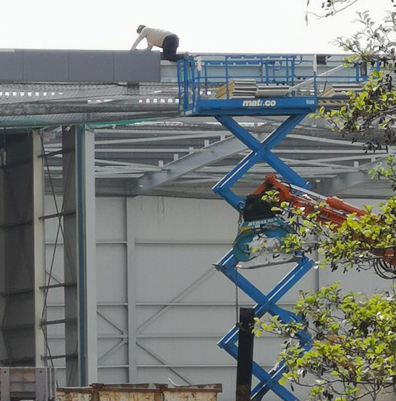 Picture of Madman crawling out of a scissor lift on to a roof