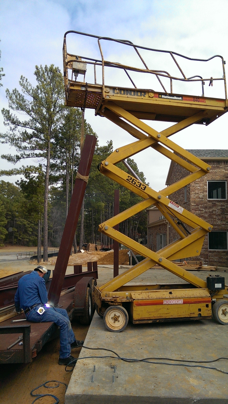 Picture of A battered scissor lift relegated to lifting girders