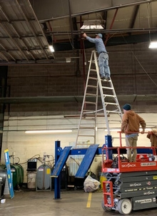 A ladder balanced on a car lift? This is a massive risk compared to using a lift like the one they already have